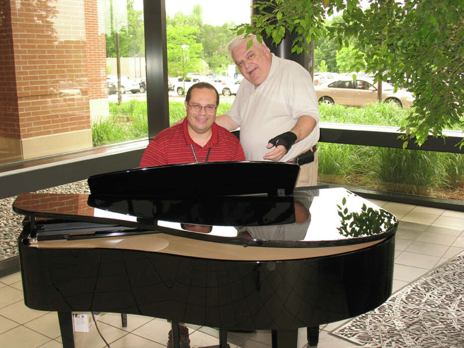 Lenin Brenes, MidMichigan employee, tries out the new piano while Howard from Herter Music Center in Bay City points out the piano's features. Photo: On 1.00