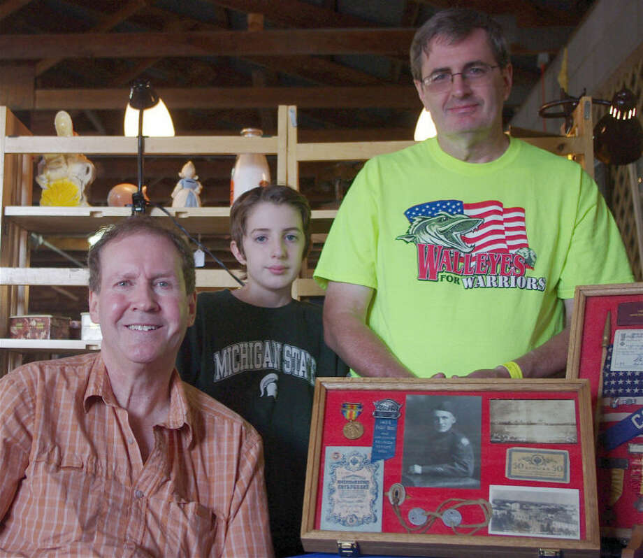 Manning the Michigan Traveling Military Museum's booth at the Michigan Antique and Collectibles Festival recently are (from left) museum director Mel Smith, 12-year-old Charlie Ray, and his father, museum president Charles E. Ray. In the foreground is a display case holding photographs and other items associated with the service of Pvt. Edward A. Harris of Essexville. He kept a diary while in an American unit known as the Polar Bears, who fought Bolsheviks in Russia. Charles E. Ray is Harris' grandson. Photo: STUART FROHM | For The Daily News