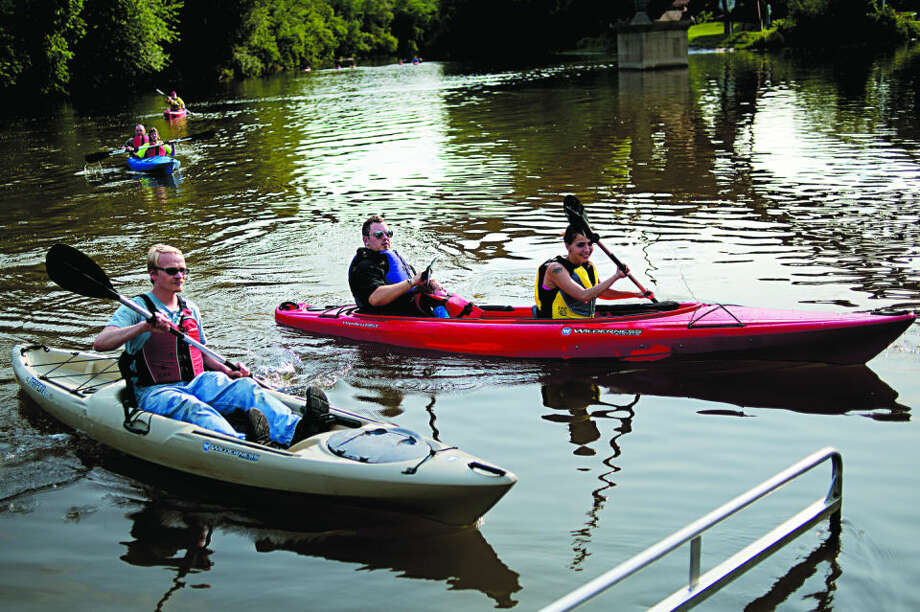 NICK KING | nking@mdn.net From left, Curt Pynnonen, Arron Carrigan, his son Dominic, 2, and Jessica Cunningham pull into the dock after kayaking on the Tittabawsee River Friday during River Days in Midland. The group rented kayaks from Ike's Mobile Kayak Rentals. Photo: Nick King/Midland  Daily News