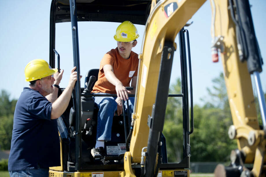 Noah Frick, 14, of Midland, listens as instructor Gerry Kenyon explains how to operate an excavator at a trades camp in Midland. On Thursday, the final day of the camp, the yoiuths were allowed to operate various types of machinery under adult guidance. Photo: NEIL BLAKE | Nblake@mdn.net