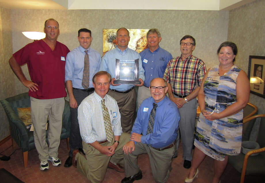 State Sen. John Moolenaar holds his 2014 Legislator of the Year Award from the Michigan Dental Association while posing with Midland dentists. Back row, from left, are: Dr. Jeff Dulude, Dr. Dan Clement, Moolenaar, Dr. Bob Klomparens, Dr. Roger Mead and Dr. Shelly Jones. Front row, from left: Dr. Larry Lang and Dr. John Carter. Photo: Photo Provided