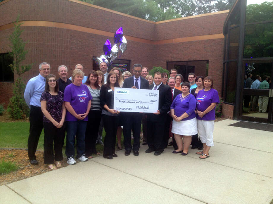 Representatives from the American Cancer Society and MEGlobal hold a $25,000 check that was presented to the society. The company made the donation in memory of Andrew Veith, an employee who died of cancer in 2012. Photo: Photo Provided