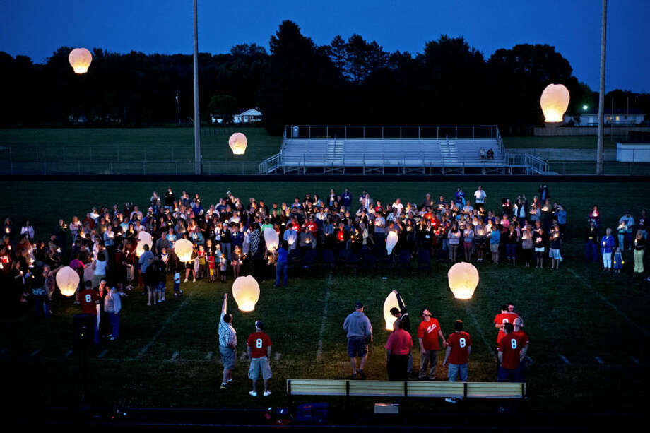 """Attendees hold candles and launch Chinese lanterns Thursday during a candlelight vigil for Reed Phillips at Bullock Creek High School. Phillips died on Saturday in a single-engine airplane accident in North Elba, N.Y. """"You never expect this to happen to such a nice guy,"""" Brian Starks, who graduated from Bullock Creek with Phillips, said. """"I guess the good do die young."""" Photo: SEAN PROCTOR 