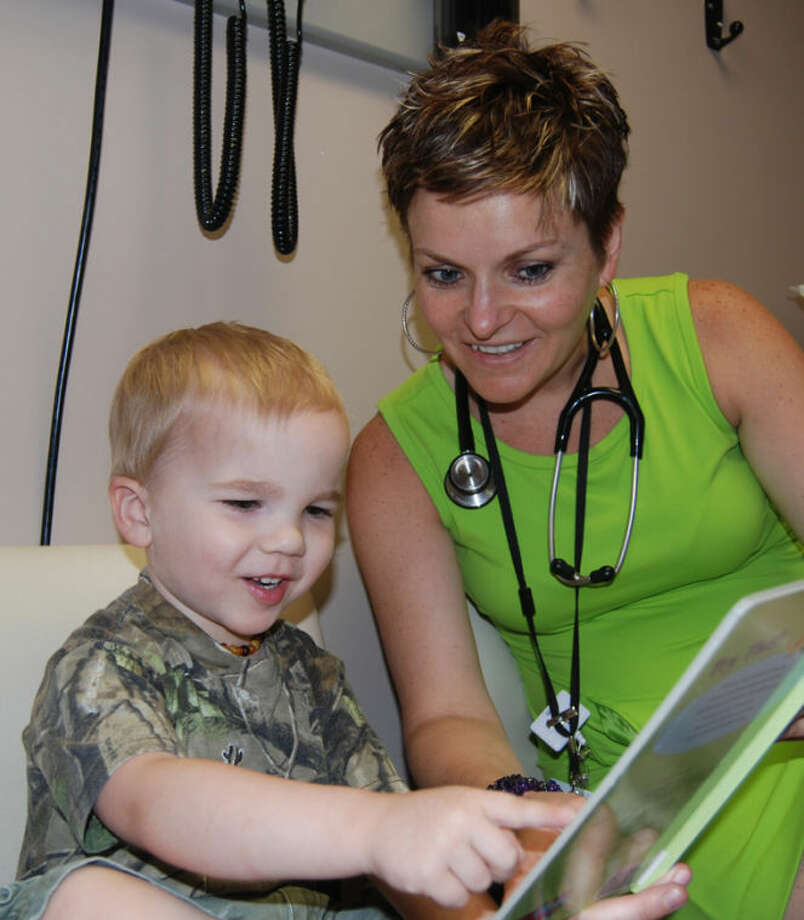 Family Medicine Physician Monika Herdzik, with MidMichigan Medical Center-Gladwin, reads to Jaden Dear of Gladwin during a recent well-child visit. Herdzik is one of the medical center providers who are providing books to young children during visits to their offices. Photo: Photo Provided