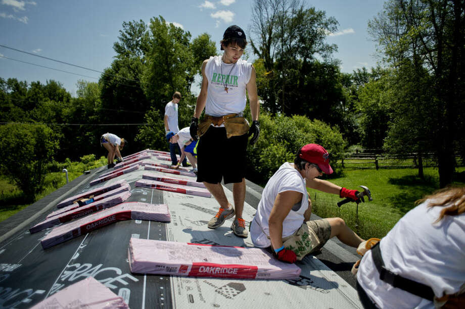 Volunteer Adam Dilley, 17, of Richmond Wis., center, looks on as leader Tina Requenez, of Houston, Texas, right, works on installing shingles with the group, from left, Madie Mealey, 15, of Indianola, Iowa, Grant Connolly, 14, of Downers Grove, Ill., Ryan Dueker, 16, of Des Moines, Iowa, and Mackenzie Weberg, 18, of Wallingford, Conn. They were putting a new roof on Donald Sian's home off Homer Road. Photo: NICK KING | Nking@mdn.net