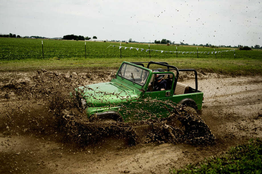 """Luke Grappin of Auburn slams into the mud pit in """"Frogger,"""" his wife Pamela's Jeep, during the sixth annual Auburn Cornfest Mud Bog on Saturday. Photo: NEIL BLAKE   Nblake@mdn.net"""
