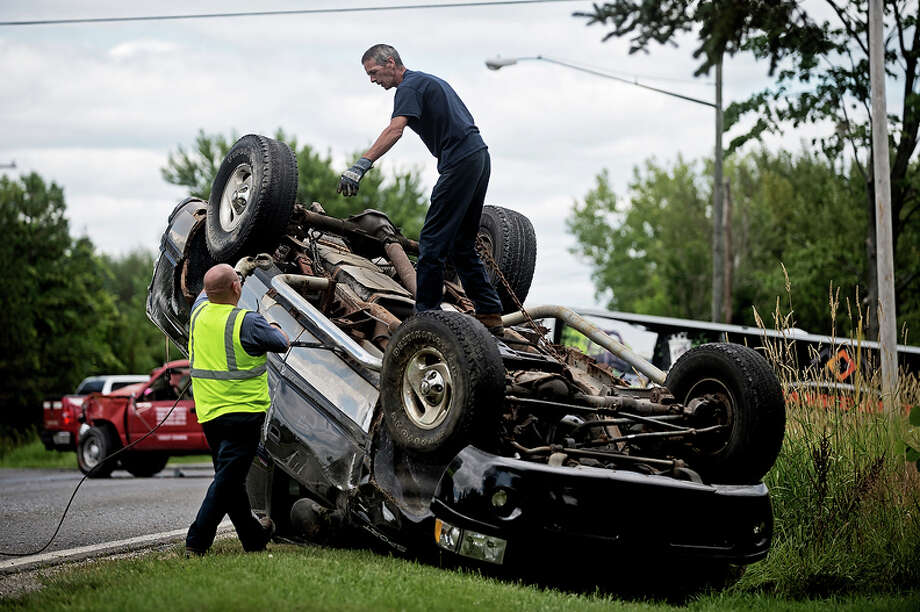 Terry Parsons, center, of Beehr Towing, prepares to flip over an overturned pickup truck Thursday at the intersection of Waldo Avenue and Hubbard Road. Photo: Sean Proctor/Midland Daily News / (c)Sean Proctor 2013