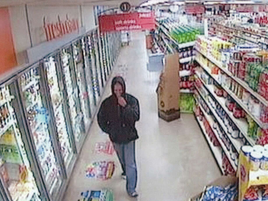 Photos released by detectives show the suspect walking past coolers while wearing the Carhartt jacket with the hood up. Photo: Photo Provided
