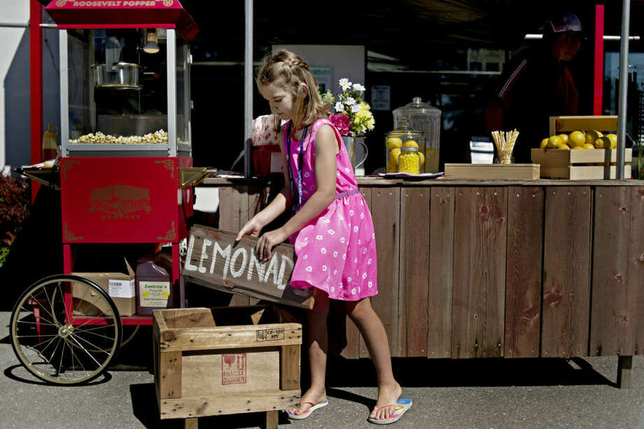 Sydney Damude, 6, holds up a sign for lemonade Friday morning outside Ace Hardware in downtown Midland. Sydney and her brother, Easton, 8, are raising money through the lemonade stand to send children to the Royal Family Kids Camp. The stand also helps keep them occupied and away from electronics during the summer. Photo: SEAN PROCTOR | Sproctor@mdn.net