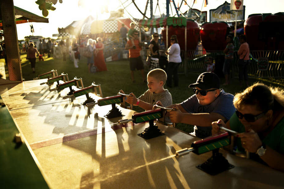 "Casey Helmreich, of Linwood, far right, places the ""Water Game"" with her two sons Brett, 12, and Brendan, 7, Thursday evening during the Auburn Cornfest. The event continues throughout the weekend with carnival games, food and live entertainment. Photo: Sean Proctor/Midland Daily News"