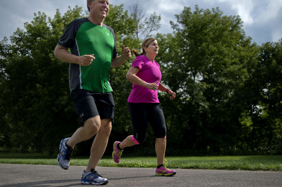 Sherry Mitchell, right, and Carl Ahearn run on the rail-trail near the Tridge in Midland. The two neighbors run together and take spinning classes. When the weather is nice they prefer running or biking outside. Photo: NICK KING | Nking@mdn.net