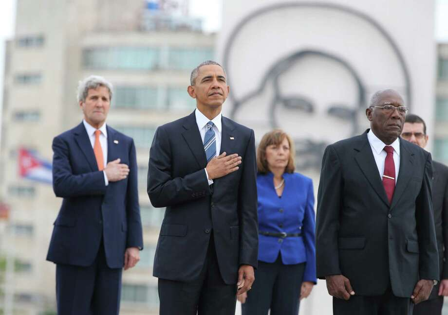 "U.S. President Barack Obama, center, and Secretary of State John Kerry, left, listen to the U.S. national anthem during a ceremony at the Jose Marti monument in Revolution Square in Havana, Cuba,  Monday, March 21, 2016.  At right is Salvador Valdes Mesa Vice-President of Cuba's State Council. ""It is a great honor to pay tribute to Jose Marti, who gave his life for independence of his homeland. His passion for liberty, freedom, and self-determination lives on in the Cuban people today,"" Obama wrote in dark ink in the book after he laid a wreath and toured a memorial dedicated to the memory of Jose Marti. (AP Photo/Enric Marti) ORG XMIT: XEM102 Photo: Enric Martí / AP"