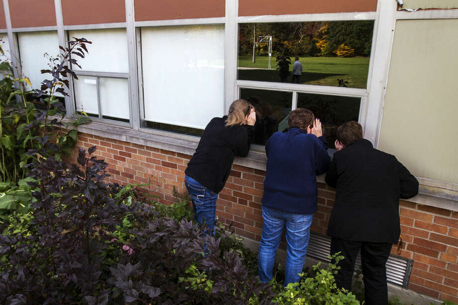 """Former Cook Elementary School teachers Cheryl Janson Collins, Charlotte Rudell and Debbie Chernick peer inside a window looking into the old art classroom taught by Rudell during a gathering of former Cook Elementary School teachers, students and parents on Wednesday. """"From the outside it looks just like another building but inside it's a family,"""" said Sharon Wesolowski, former Cook Elementary School teacher. Cook Elementary School is set to be torn down later this year. Photo: Theophil Syslo 