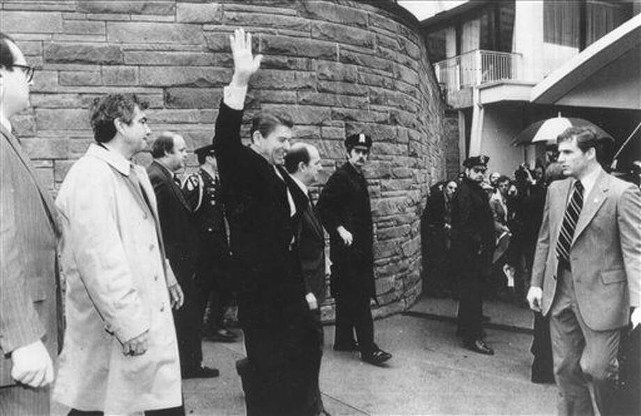 In this March 30, 1981 file photo provided by The White House, President Ronald Reagan waves just before he is shot outside the Washington Hilton in Washington. From left are secret service agent Jerry Parr, in raincoat, who pushed Reagan into the limousine; press secretary James Brady, who was seriously wounded; Reagan; Michael Deaver, Reagan's aide; unidentified policeman; Washington policeman Thomas K. Delahanty, who was shot; and secret service agent Timothy J. McCarthy, who was shot in the stomach. Jerry Parr, the retired Secret Service agent credited with saving President Ronald Reagan's life on the day he was shot outside a Washington hotel has died. Photo: The White House Via AP