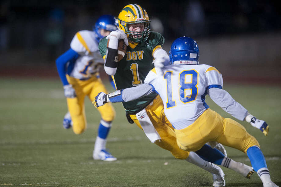 BRITTNEY LOHMILLER | blohmiller@mdn.net Midland High's Luke DeLong tackles Mike Robb of Dow High in the first half of the Friday night game at the Midland Stadium. Photo: Brittney Lohmiller/Midland Daily News