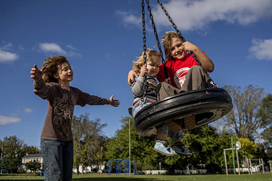 Max Kidder, 8, swings brothers Alerci, 2, and Alexei Suppes, 8, on the tire swing as their mothers watched on Thursday at Carpenter Street School playground. Photo: ERIN KIRKLAND | Ekirkland@mdn.net