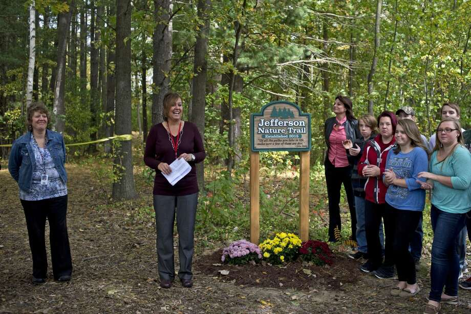 Jefferson Middle School teacher Jane Camilletti, center, addresses the crowd gathered to commemorate the new Jefferson Nature Trail as fellow teachers Claudia Warren, left, and Jennifer Lehman, right, watch on Tuesday. The project, which was conceived by teachers Camilletti, Christie Gayheart, Lehman and Warren, was funded by two Gerstacker Foundation grants and community support. The school will use the trail as an outdoor classroom. Photo: Erin Kirkland | Midland Daily News
