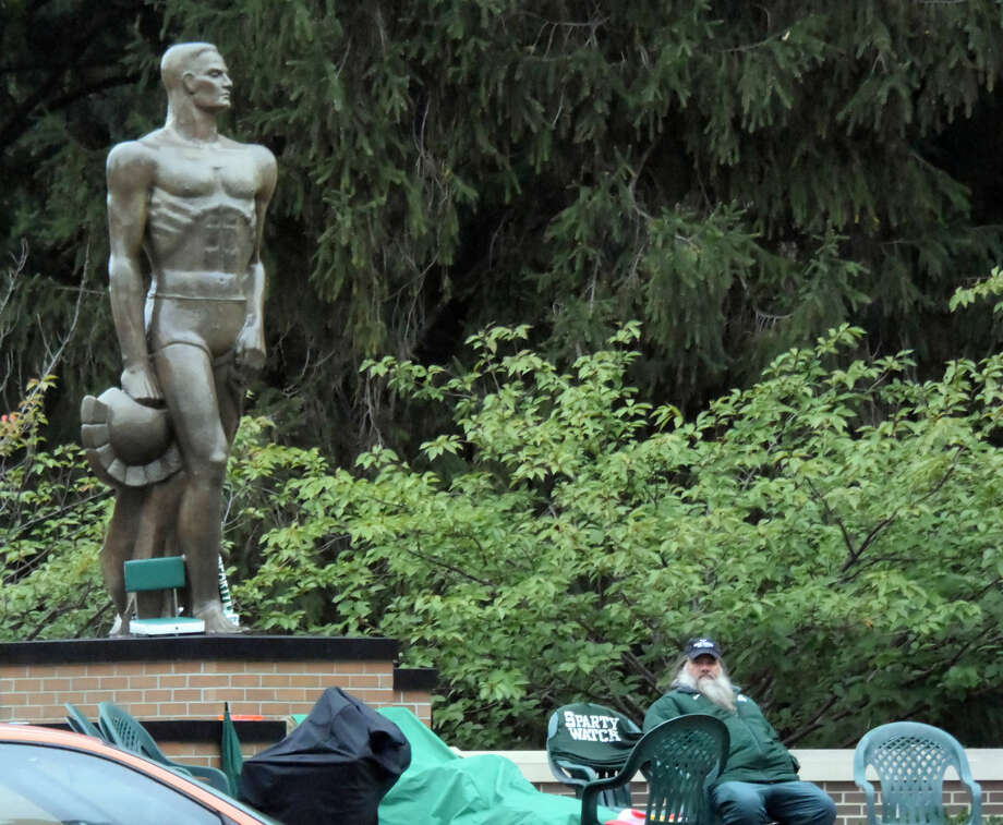 In this photo taken on Tuesday, Oct. 13, 2015, in an effort to prevent pranks from cross state football rival the University of Michigan, a solo Spartan fan guards the Sparty statue on Michigan State University's campus in East Lansing, Mich. on October 13, 2015. The two schools meet on the gridiron this Saturday. (Dale G. Young/Detroit News via AP) Photo: Dale G. Young
