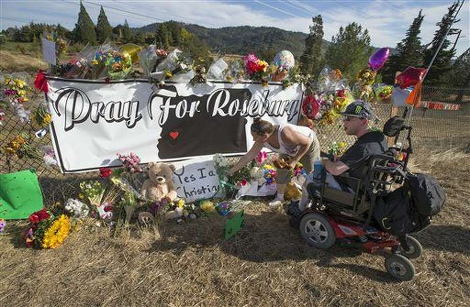 Candida Miller, left, and Brandon Snyder leave flowers at a site of a growing memorial to victims of the mass shooting at Umpqua Community College in Roseburg, Ore., Tuesday. Photo: AP Photo Via Chris Putsch   The Register-Guard