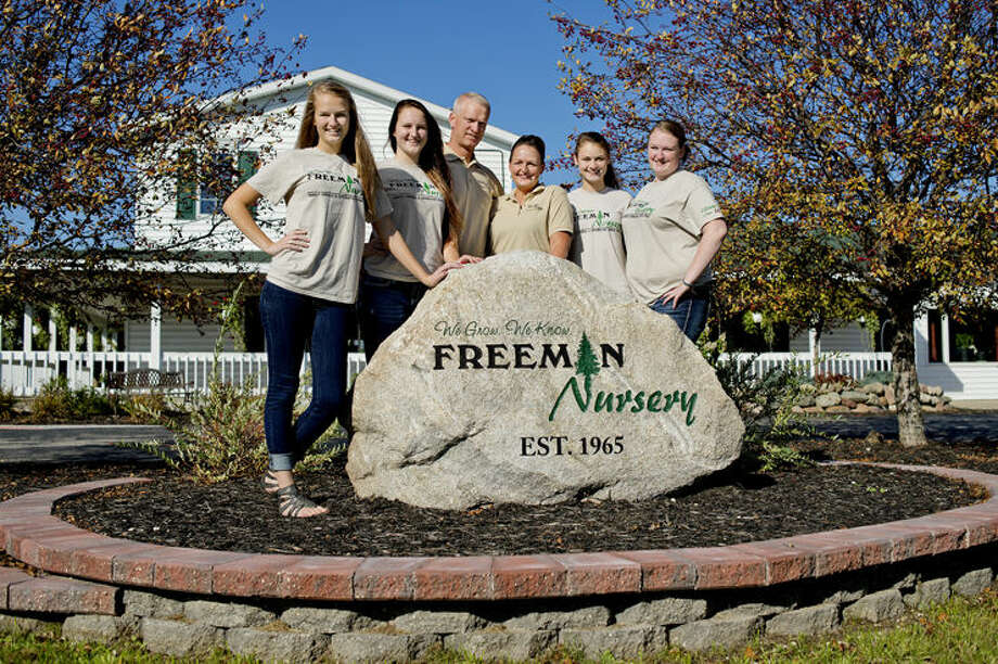 Mike and Kim Shea, center, with their daughters, from left, Kennedy, 18, Clarity, 16, Century, 15, Cassaday, 21, pose near the Freeman Nursery rock on their property in Beaverton. Kim took over her father's business which is celebrating its 50th anniversary of being family run. Kennedy is intending to take over the business in a few years as third generation owner. Photo: Nick King/Midland Daily News