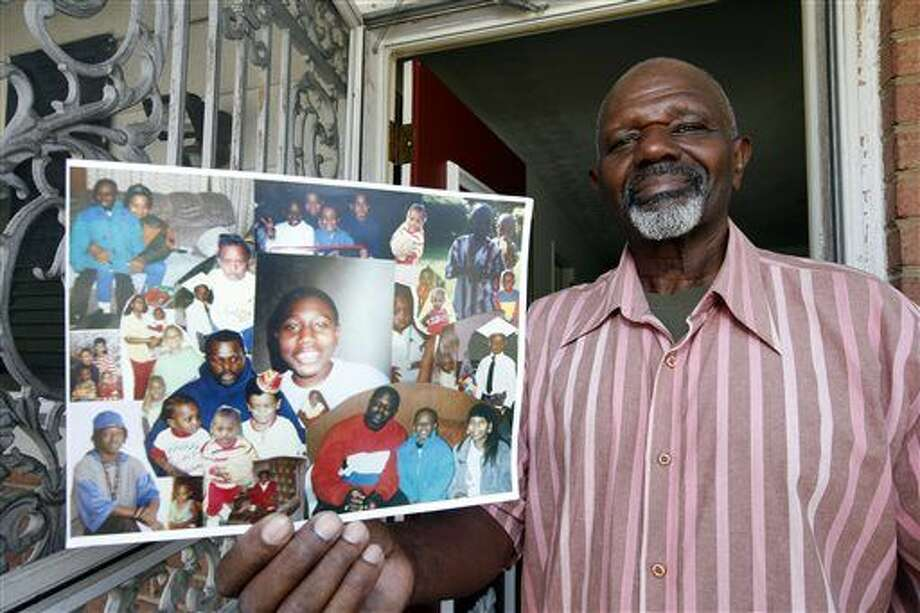 Kenneth Evans holds a composite of photographs of his son, Tuan Evans, as he poses for a photograph at his home in Temple Hills, Md. Drug criminals once described by prosecutors as unrepentant repeat offenders are among those poised to benefit from new sentencing guidelines that are shrinking punishments for thousands of federal prisoners, according to an Associated Press review of court records. Tuan Evans is scheduled for early release from prison, the result of new sentencing guideline ranges that trim punishment lengths for convicted drug criminals. Photo: Alex Brandon   AP Photo
