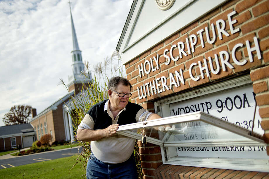 Jim Pugh cleans the inside of the glass that covers the sign at the Holy Scripture Lutheran Church on Monday in Midland. Photo: Nick King | Midland Daily News