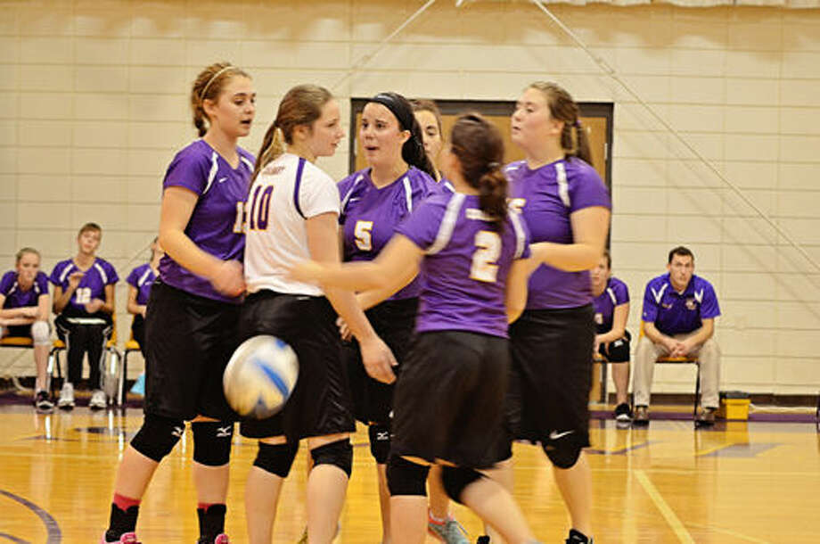 The Calvary Baptist volleyball team huddles during Tuesday's quarterfinal match at the Kings' gym.