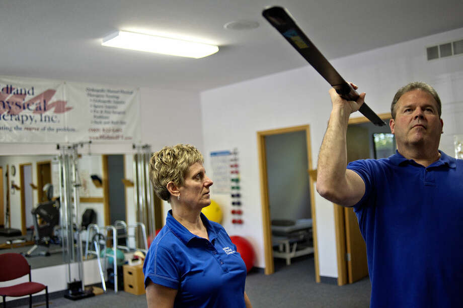 Owner Sheila Isles-Truax, left, works with client Mike Mishic on Monday at Midland Physical Therapy. Mishic has seen a great improvement in his shoulder pain since working with Isles-Truax for two weeks. This October marks the 20th anniversary of Midland Physical Therapy. Photo: NICK KING | Nking@mdn.net