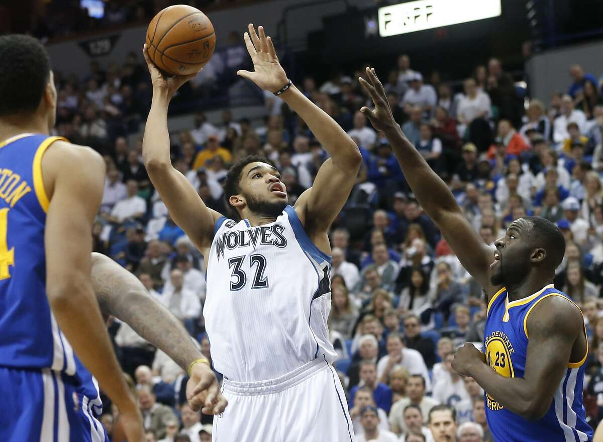 Minnesota Timberwolves� Karl-Anthony Towns, left, shoots as Golden State Warriors� Draymond Green, right, defends in the first quarter of an NBA basketball game Monday, March 21, 2016, in Minneapolis. (AP Photo/Jim Mone)