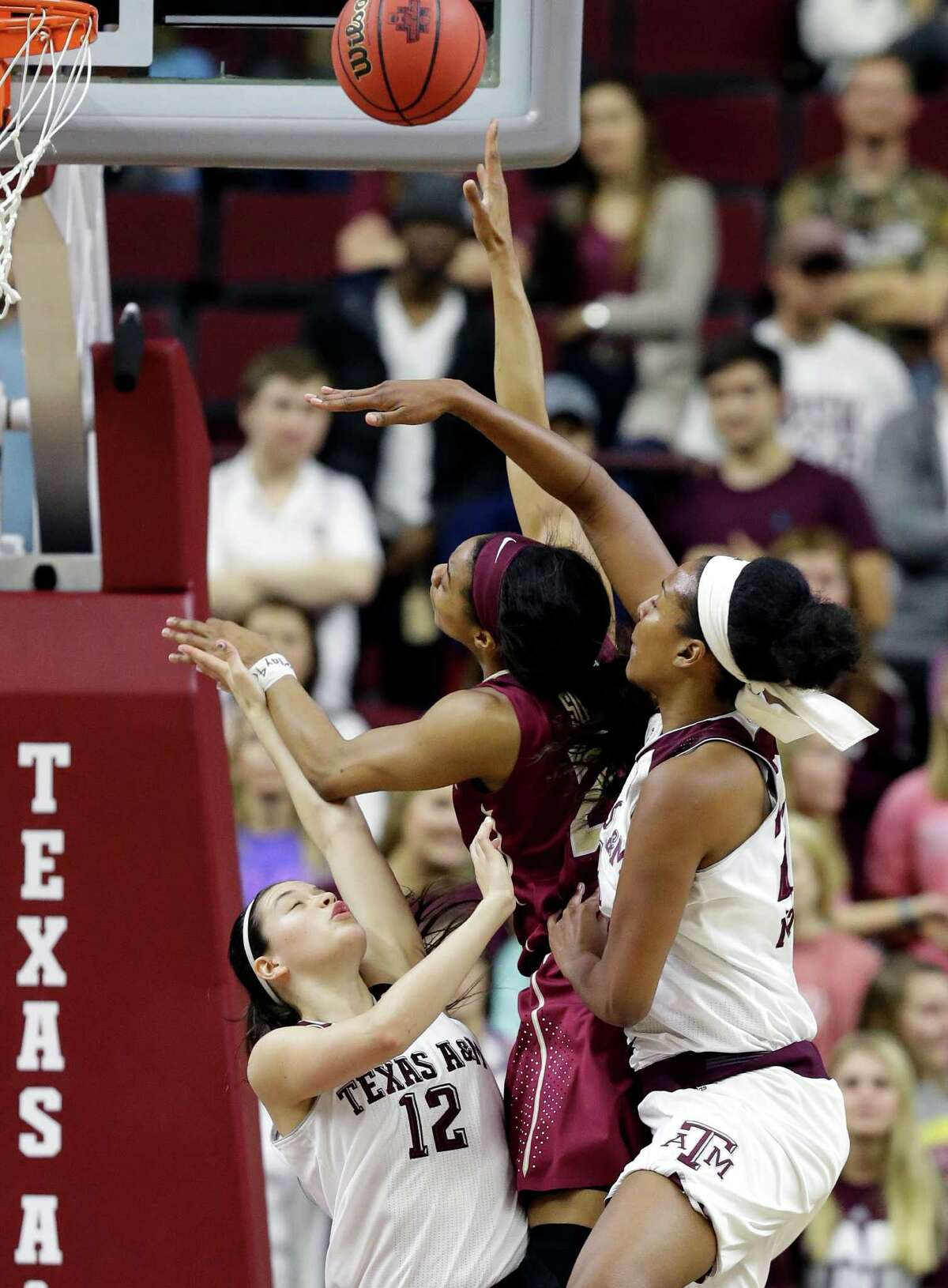 Florida State's Ivey Slaughter, who had 10 points and nine rebounds, is sandwiched between Texas A&M's Danni Williams (12) and Rachel Mitchell in the first half.
