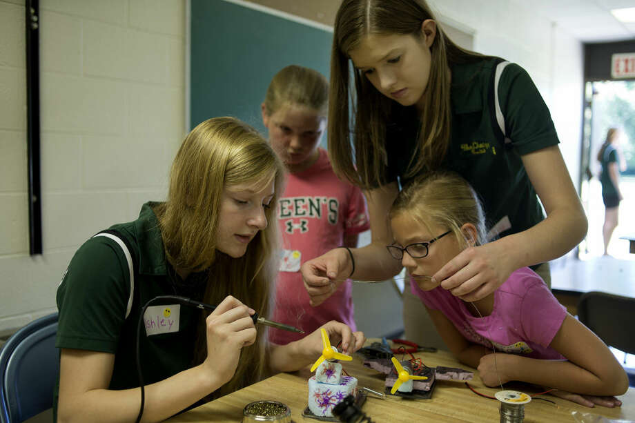 Members of the Dow High FIRST Robotics Team 2619 Ashley Brenton, 17, left, and Bailey Flint, 17, help 8-year-old Lexie Thornhill, of Jackson, and Ava Brown-nall, 8, of Midland, sodder wires to the engine on their mag-lev car during the STEM exploration camp Tuesday morning at the Franklin Center. The camp, hosted by Dow's robotics team, runs through Thursday and teaches students in third to sixth grade about science and math through interactive projects. Photo: BRITTNEY LOHMILLER   Blohmiller@mdn.net
