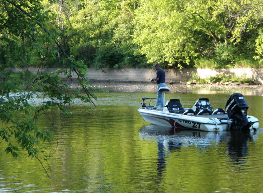 An angler in a bass boat fishes the Tittabawassee River near Emerson Park in a past season. The river and its fishing have both drawn better reviews in recent decades. Photo: Steve Griffin | For The Daily News