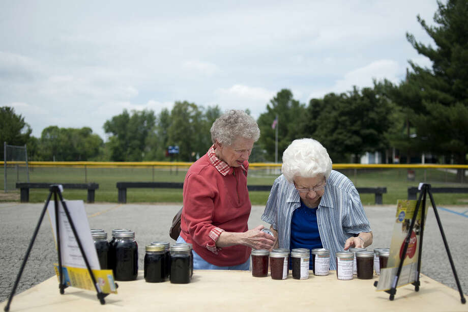 Sandra Simmons, left, of Lee Township, and Blanche Stark, of Homer Township, look at jams and maple syrup made by Snappy's Sweets during the Sanford Farmers Market Thursday afternoon. The Sanford Farmers Market in the Sanford Village Park runs from 1-5 p.m. on Thursdays, with a noon to 1 p.m. set up time for vendors, and 7 a.m. to 1 p.m. on Mondays, with a vendor setup time from 6-7 a.m. Vendor fees are $5. Photo: Brittney Lohmiller | Blohmiller@mdn.net