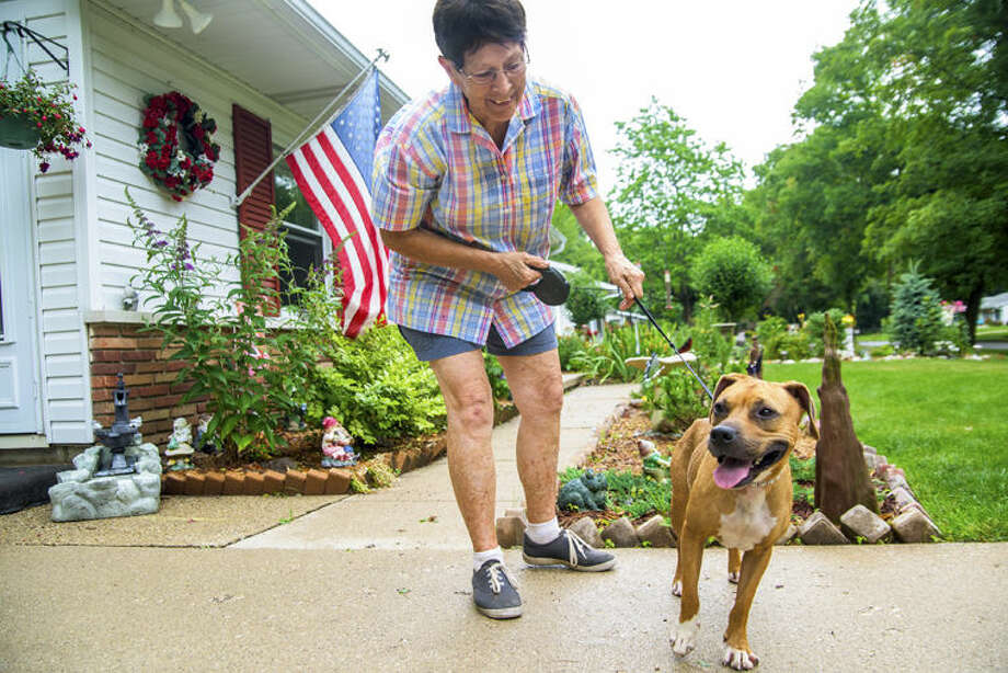 Sharon Duford plays with her newly adopted dog, Jasmine, at her Midland home. Duford adopted the mixed breed from the Humane Society of Midland County. Photo: Danielle McGrew/for The Daily News
