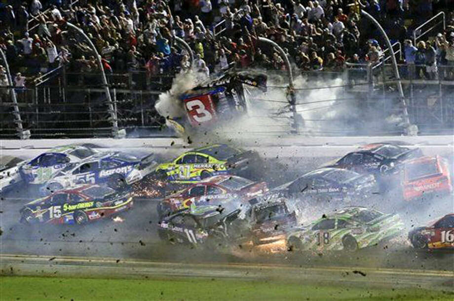 Austin Dillon (3) goes airborne and hits the catch fence as he was involved in a multi-car crash on the final lap of the NASCAR Sprint Cup series auto race at Daytona International Speedway, Monday, July 6, 2015, in Daytona Beach, Fla. (AP Photo/Terry Renna) Photo: Terry Renna