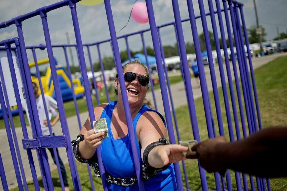 Sarah Harris, raises $5 in order to be release from jail during Relay For Life on Saturday at the Midland County Fairgrounds. Photo: Nick King | Nking@mdn.net