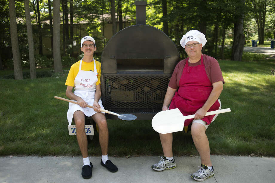 BRITTNEY LOHMILLER | blohmiller@mdn.net Jameson Baker, left, and his father Jim Baker both of Sanford make make pizza on a mobile wood fired oven Jim made with help from his brother, Tim Baker. The oven takes approximately 2 minutes to cook a pizza. Photo: Brittney Lohmiller/Midland Daily News