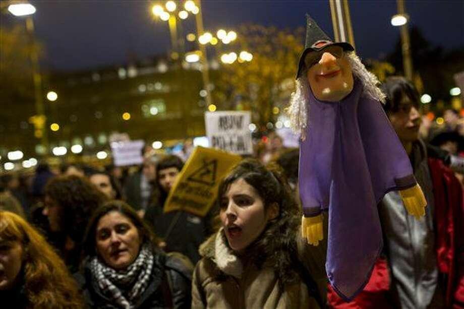 """Numerosas personas, entre las que una sostiene en lo alto un títere, se reúnen afuera del ayuntamiento de Madrid en apoyo a dos titiriteros detenidos el viernes por utilizar un letrero que decía """"Gora Alka-ETA"""", un juego de palabras que hacía referencia al grupo armado vasco ETA y a Al Qaeda en Madrid, durante una movilización el miércoles 10 de febrero de 2016. Un tribunal español ordenó el miércoles la libertad de los dos titiriteros encarcelados desde la semana pasada porque presuntamente enaltecieron el terrorismo durante un controvertido carnaval financiado con recursos públicos. (AP Foto/Francisco Seco) Photo: Francisco Seco"""