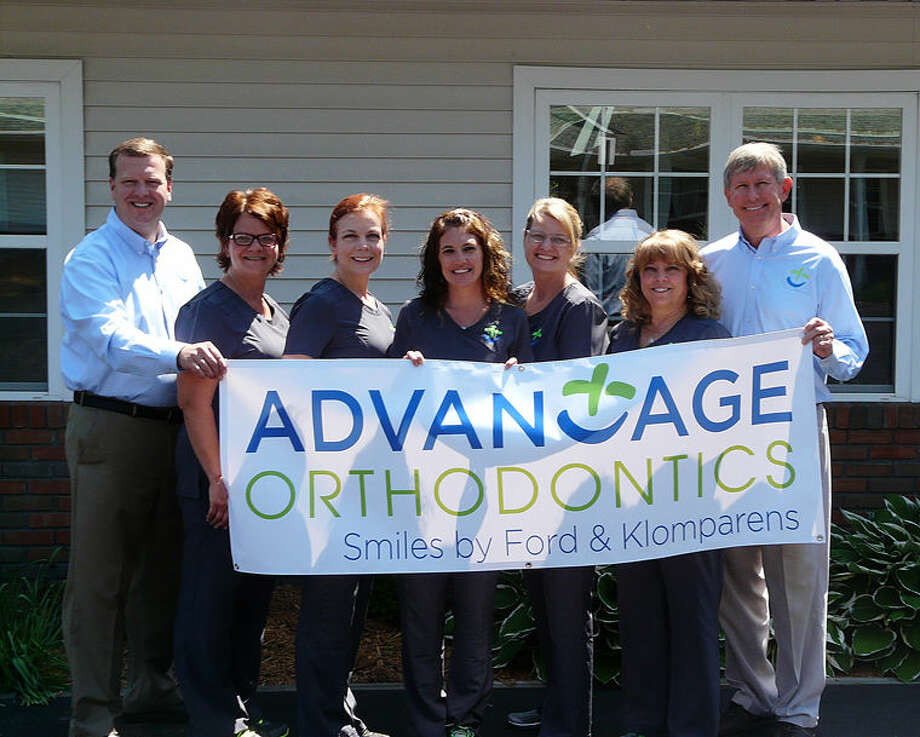 Dr. Douglas Ford, far left, and Dr. Robert Klomparens, far right, are joined by several of their staff members to display a banner with the practices' new name. After 34 years as Klomparens Orthodontics, the business has announced a name change to Advantage Orthodontics. Photo: Photo Provided