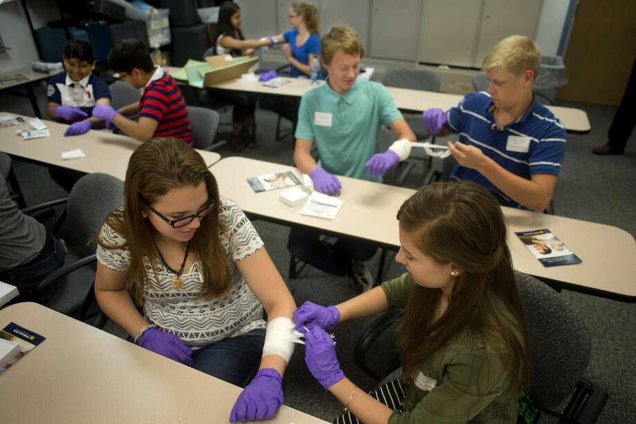 Fifteen-year-old Hope Butler, left, holds out her arm for Jessica Hedlund, 15, both of Midland, to practice bandaging wounds as part of their first aid lesson in the Grow Your Own health care career camp at the MidMichigan Emergency Medical Services station Wednesday afternoon. The program provided in-depth looks at various health care departments, job-shadowing and hands-on experience for middle and high school students interested in working in healthcare. Photo: Brittney Lohmiller | Blohmiller@mdn.net