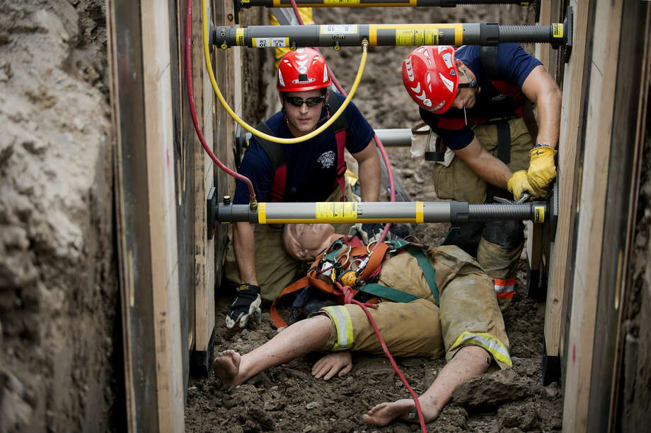 Midland Fire Department firefighter Jacob Keister, left, and Cameron Gelinas secure the walls of a trench during a rescue exercise at the City of Midland Landfill on Tuesday. Photo: Neil Blake | Nblake@mdn.net