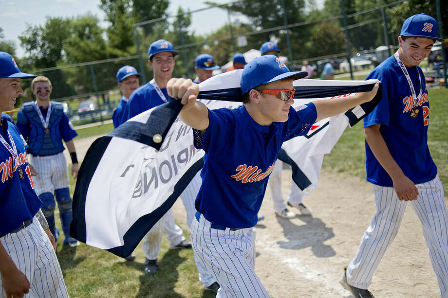 Brennan Doyle walks with the championship banner over his back while his teammates look on after Midland Northeast/Fraternal Northwest beat Sanford to win the Michigan Junior Little League district 1 championship. Photo: Nick King | Nking@mdn.net