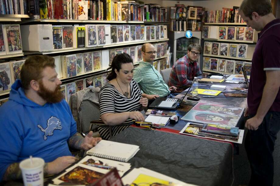 NICK KING   nking@mdn.net From left, Michigan Comics Collective members Travis McIntire, Sara Sowles, Sean Seal and Joe Freyre talk with customer customer Matt Rick, right, of Hemlock, on Saturday at Collector's Corner. The four and author Greg Wright were on hand to sign copies of the new graphic novel Wild Bullets, answer questions and draw for customers. Photo: Nick King/Midland Daily News
