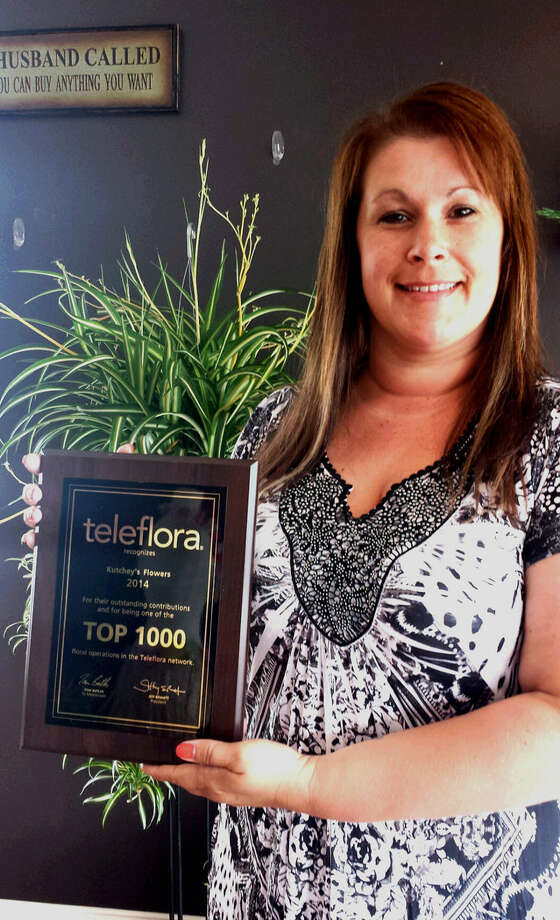 Wendy Arthur, owner of Kutchey's Flowers, holds the plaque presented by Teleflora, the world's leading flower wire service. Photo: Photo Provided