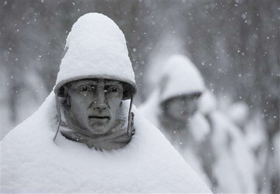 One of the 19 stainless steel statues of the Korean War Veterans Memorial is covered with snow in Washington, Monday, Feb. 15, 2016. Bitter cold was replaced by snow, sleet and rain Monday in the mid-Atlantic states and the South, but many residents were able to hunker down at home with federal offices and many businesses closed for Washington's Birthday. Photo: AP Photo/Carolyn Kaster