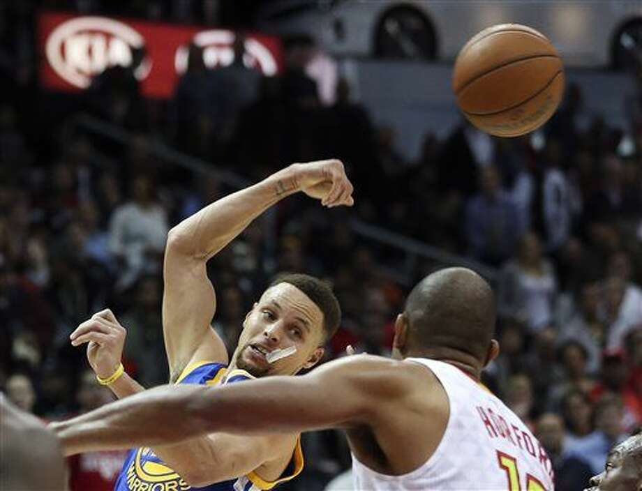 Golden State Warriors guard Stephen Curry (30) passes as Atlanta Hawks center Al Horford (15) defends in the second half of an NBA basketball game Monday, Feb. 22, 2016, in Atlanta. Golden State won 102-92. (AP Photo/John Bazemore) Photo: John Bazemore