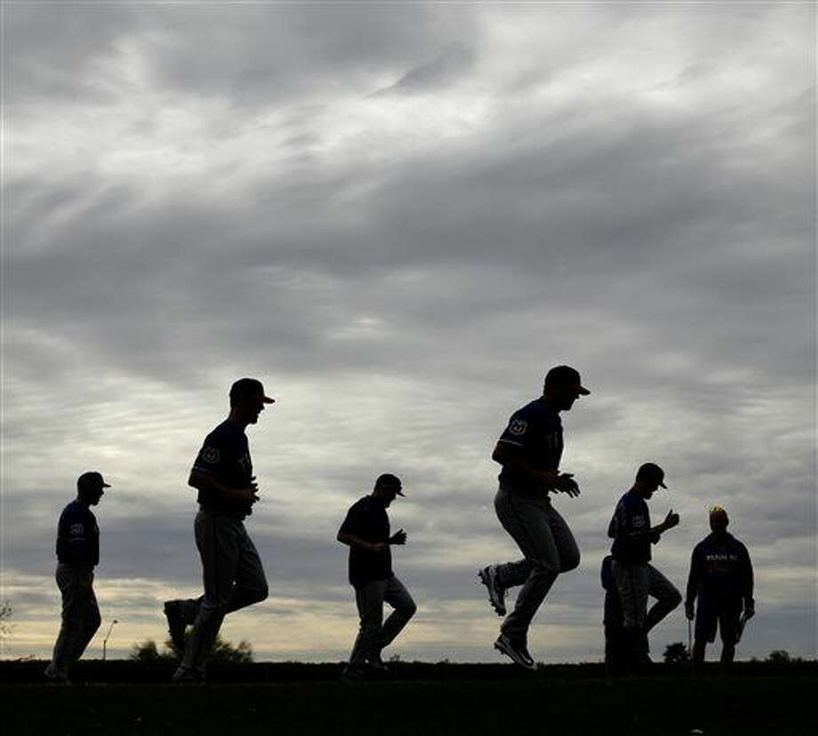 Texas Rangers players warm up before spring training baseball practice Friday, Feb. 19, 2016, in Surprise, Ariz. (AP Photo/Charlie Riedel) Photo: Charlie Riedel