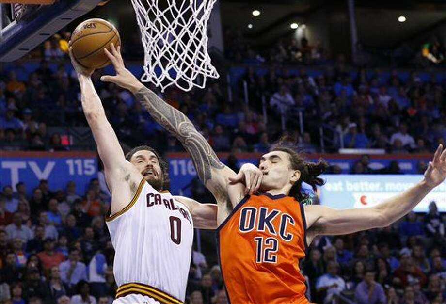 Kevin Love, de los Cavaliers de Cleveland, intenta disparar frente a Steven Adams, del Thunder de Oklahoma City, en el encuentro del domingo 21 de febrero de 2016 (AP Foto/Alonzo Adams) Photo: Alonzo Adams