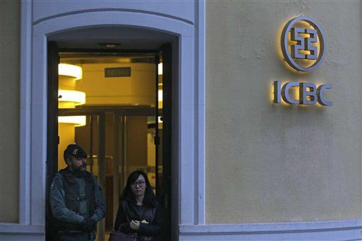 Una mujer parte de las oficinas del banco chino ICBC en Madrid, España, mientras un policía de la guardia civil monta guardia en el exterior, el miércoles 17 de febrero de 2016. (Foto AP/Francisco Seco)