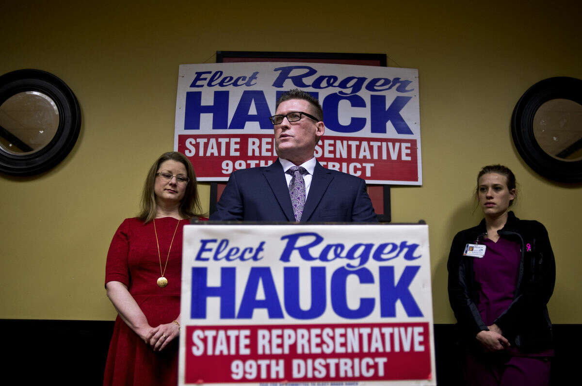 Roger Hauck, surrounded by his wife, Raschelle, left, and daughter, Stacey, right, announces his bid for the 99th House District as a Republican at Pizza Sam's on Thursday morning.